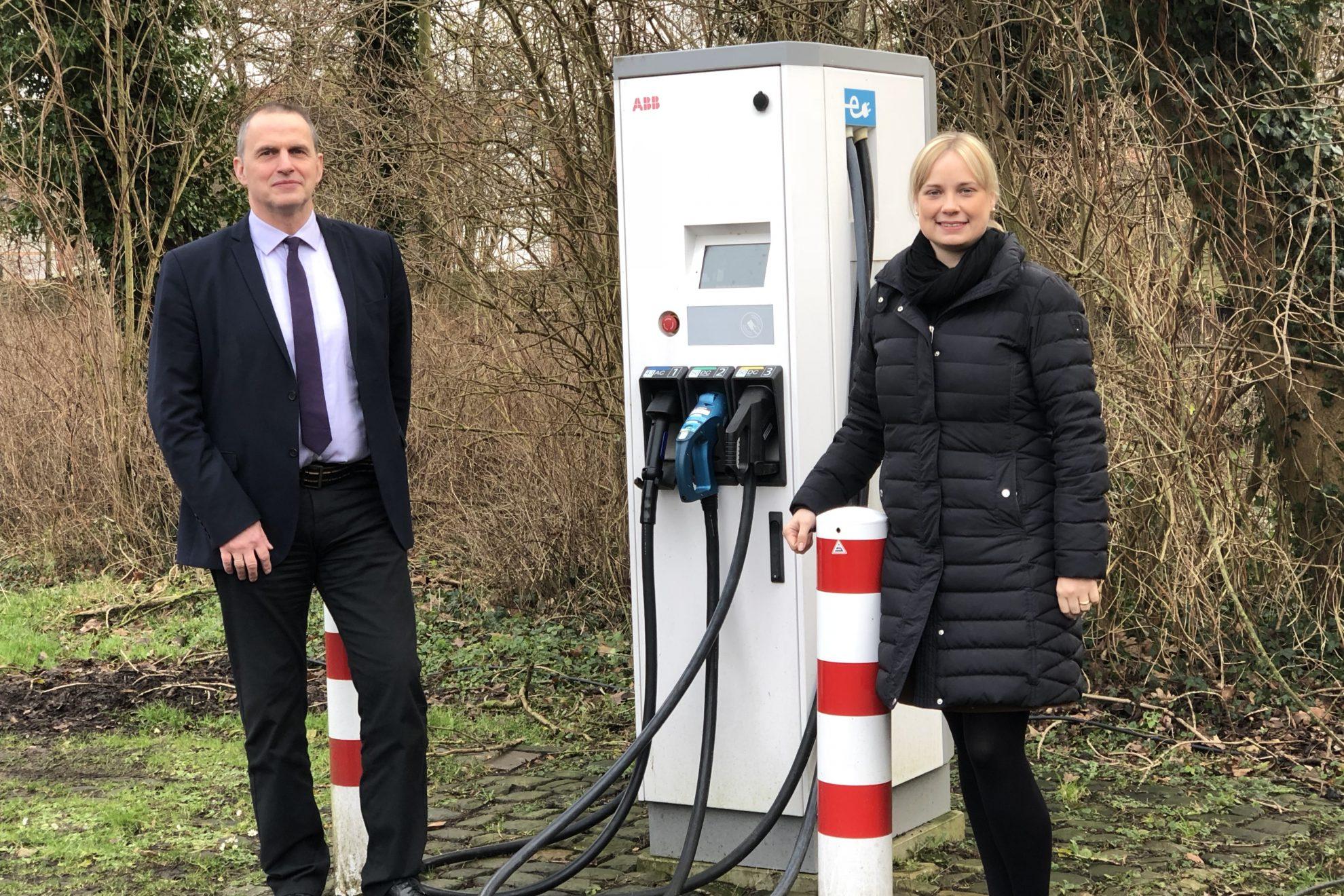Bürgermeister Weber und Bundestagsabgeordnete Völlers neben einer Ladestation für E-Fahrzeuge